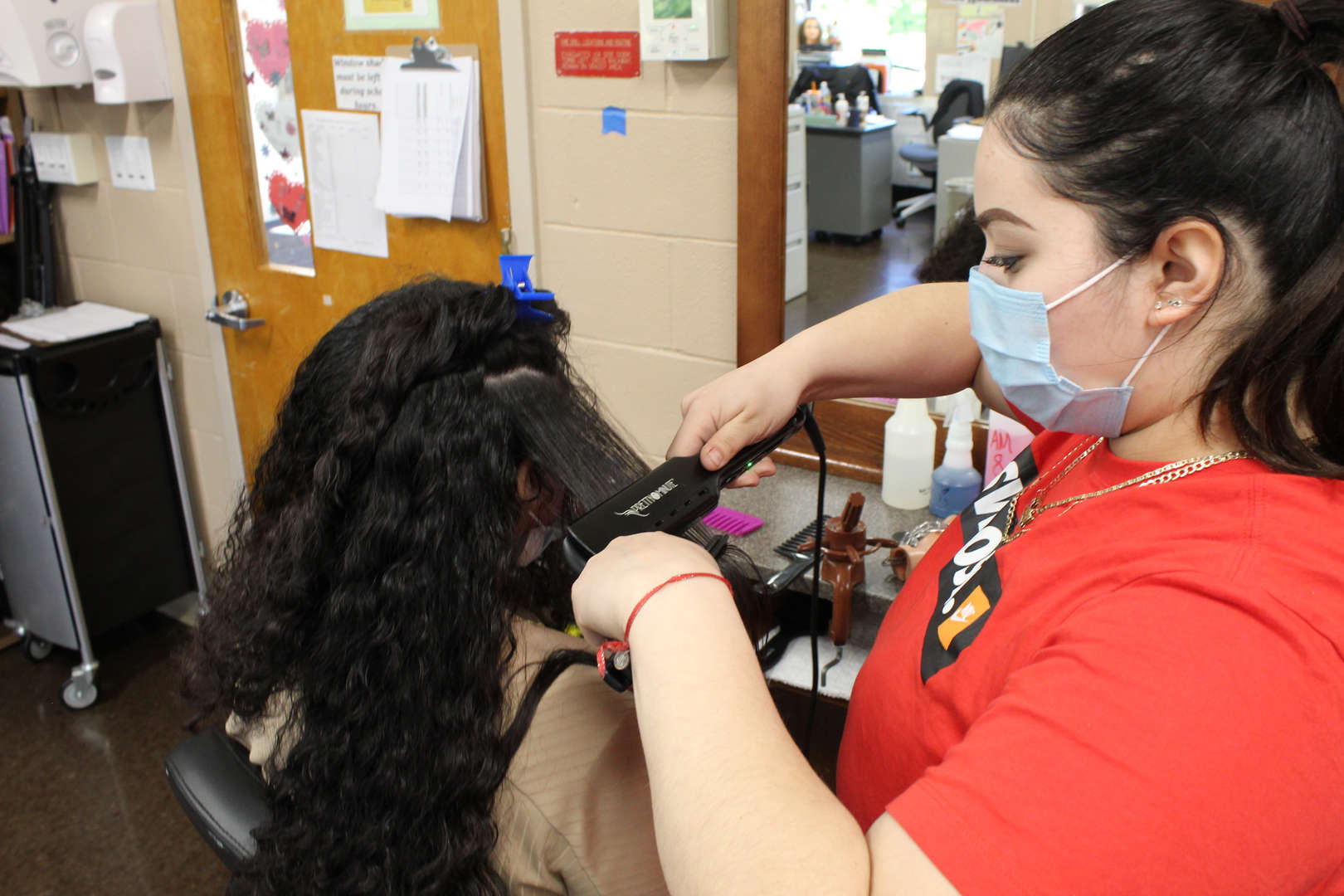 Girl straightens hair of another girl using a flatiron tool