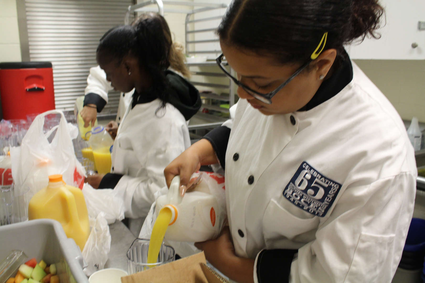 Culinary students pour orance juice