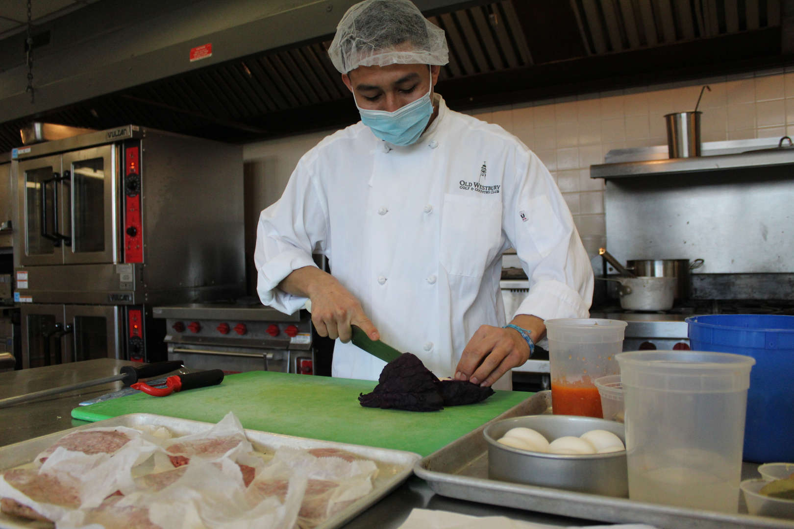 Culinary student chopping purple cabbage