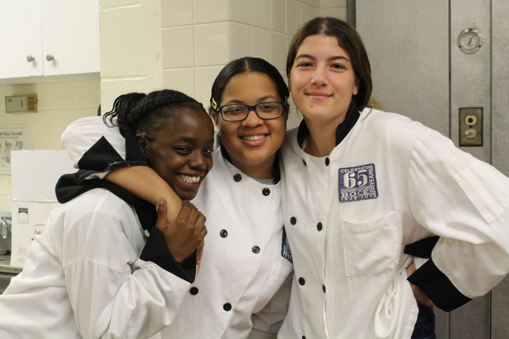 Three culinary students pose