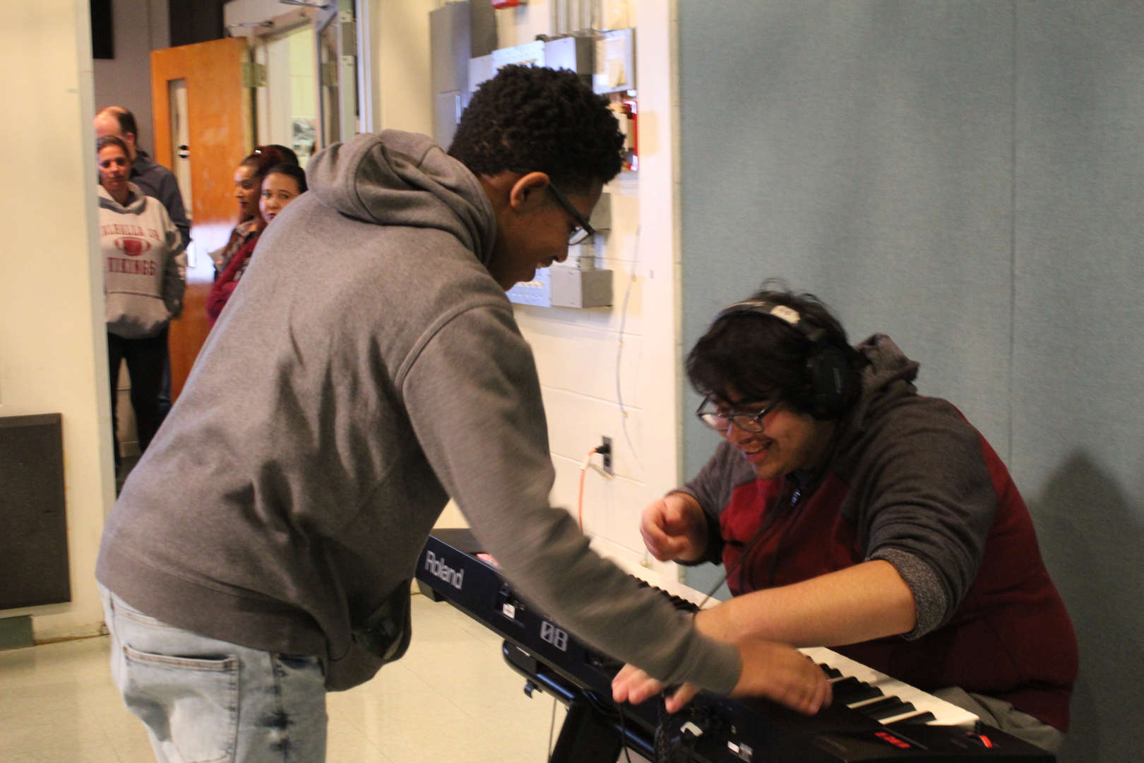 Two students, on seated, one standing, at an electronic keyboard