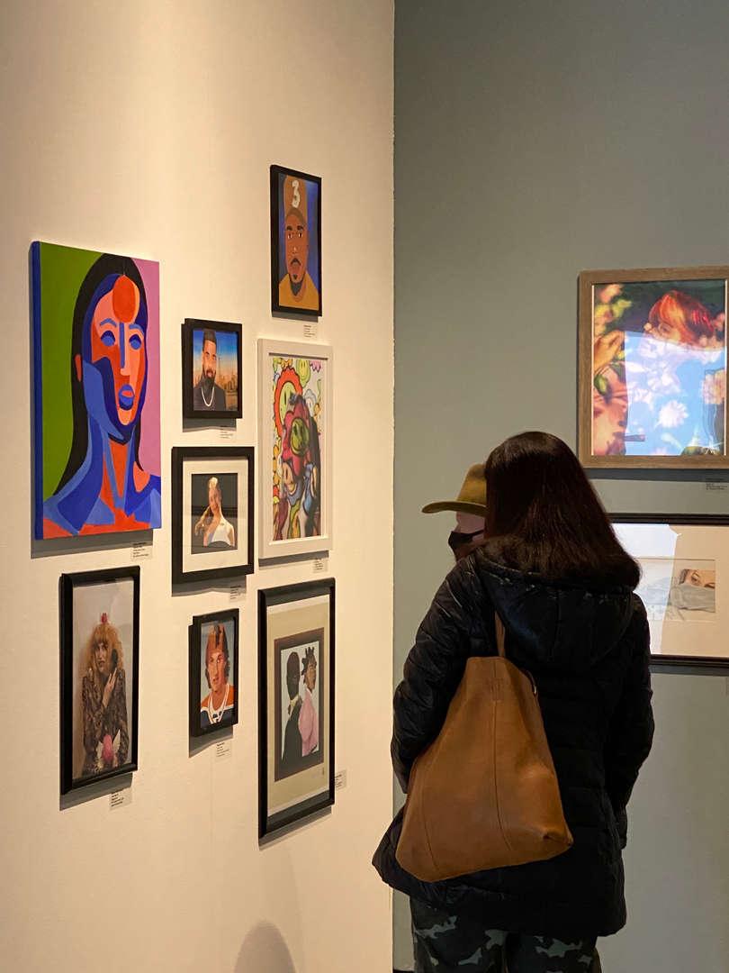 People looking at art hanging in gallery