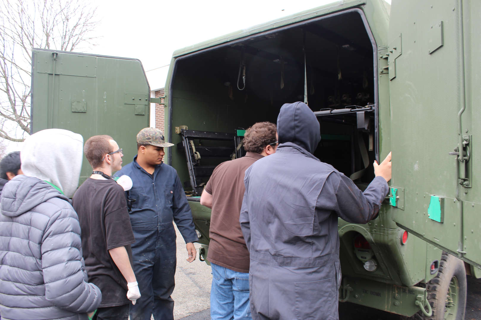 Students look in the back of a military Humvee
