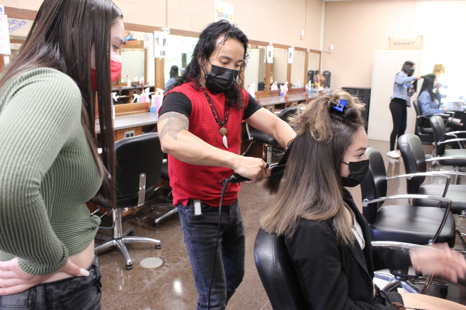 Man instructs student on how to use a flatiron tool to straighten hair