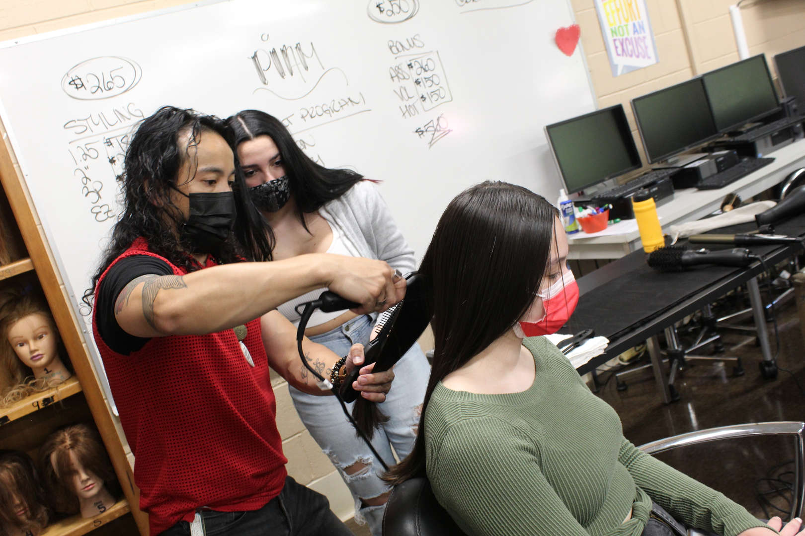 Man shows girl how to use a flatiron tool on another girl's hair
