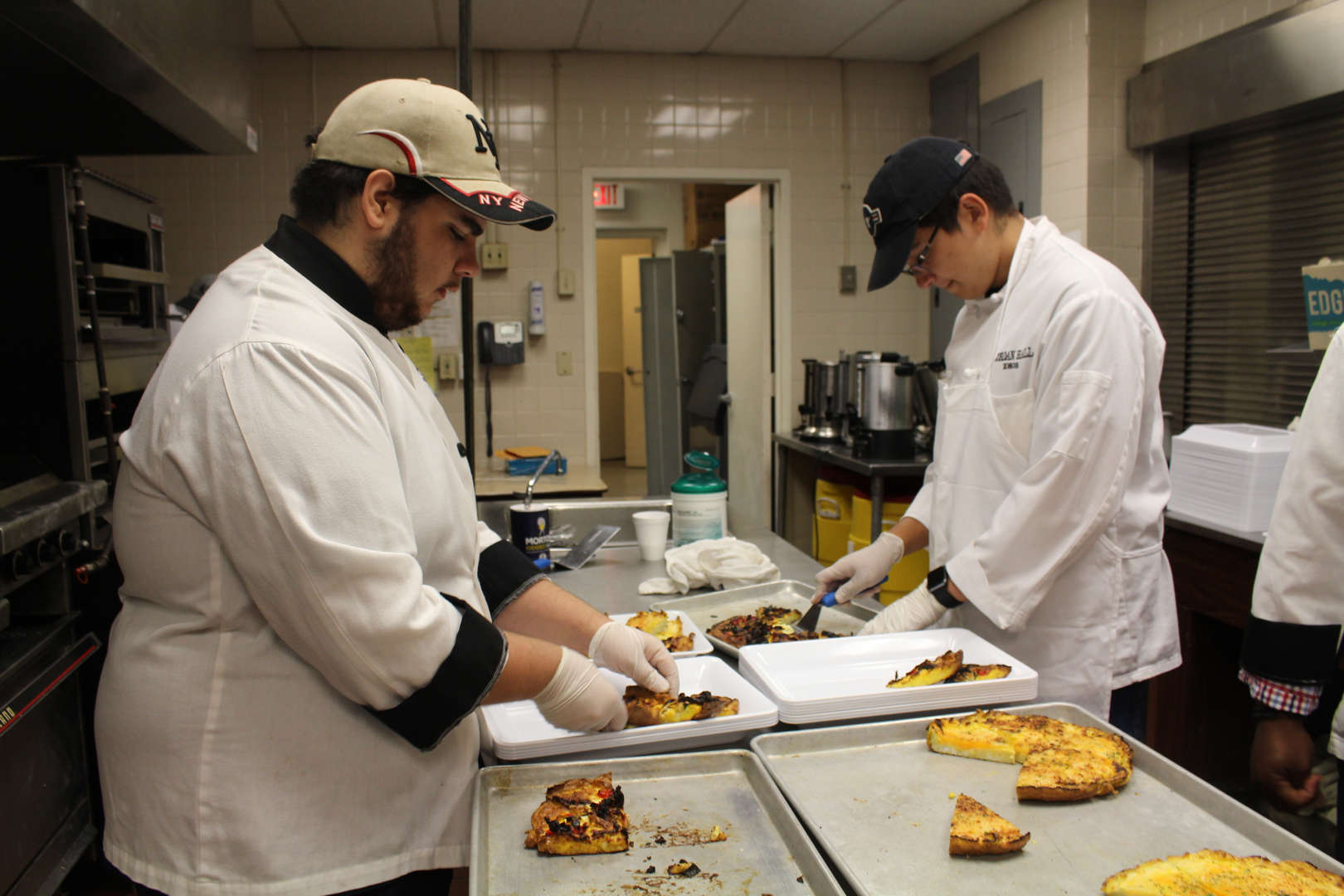 Culinary students work in the kitchen plating food