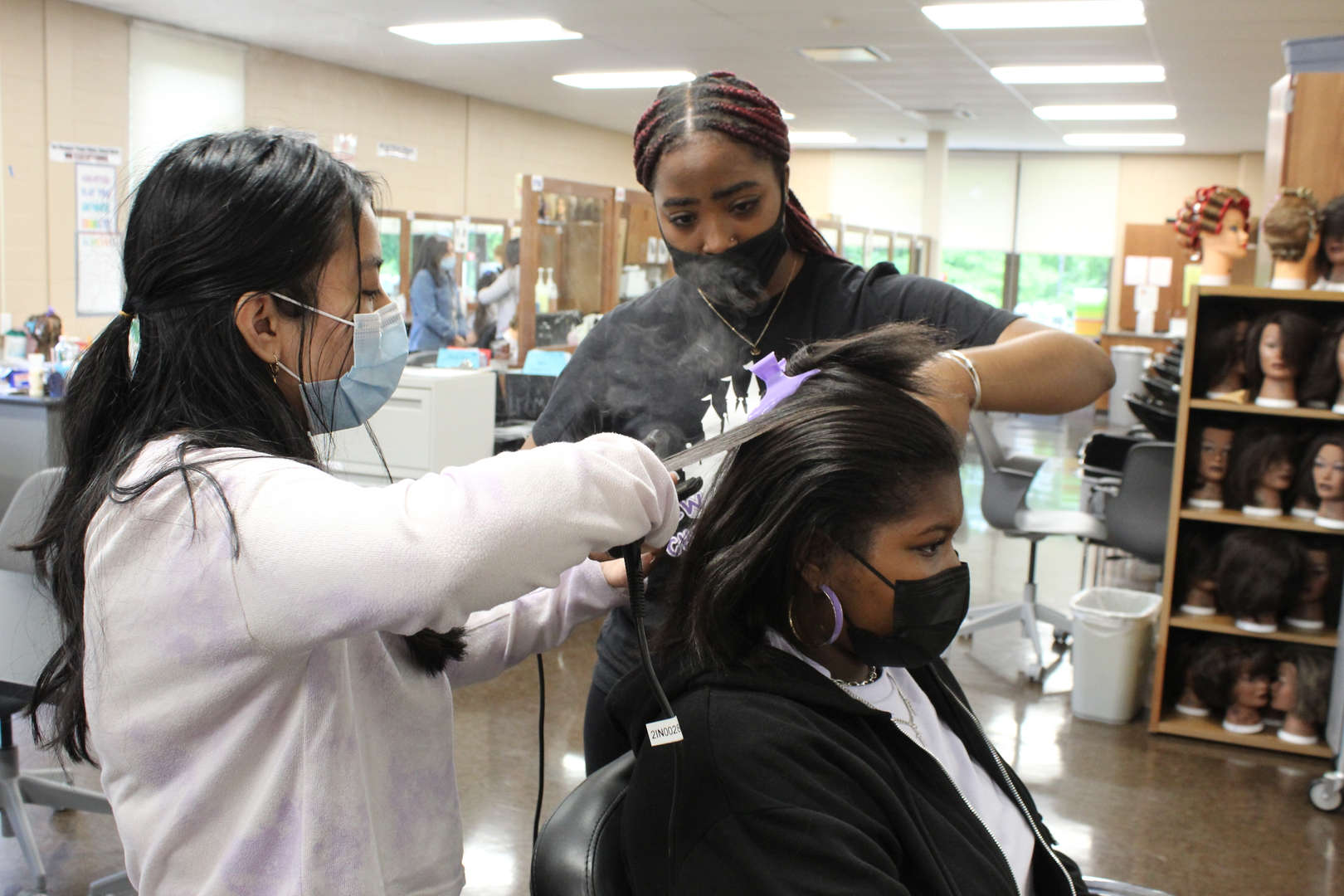 Girl using flatiron tool while another girl watches
