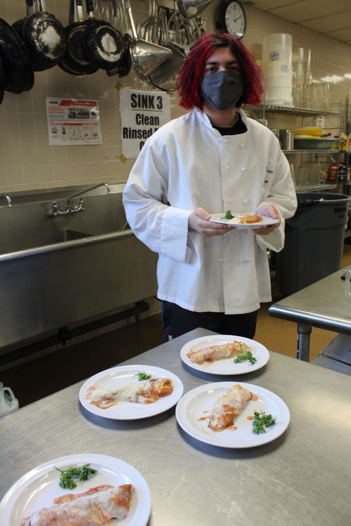 Culinary student holding a plate of food