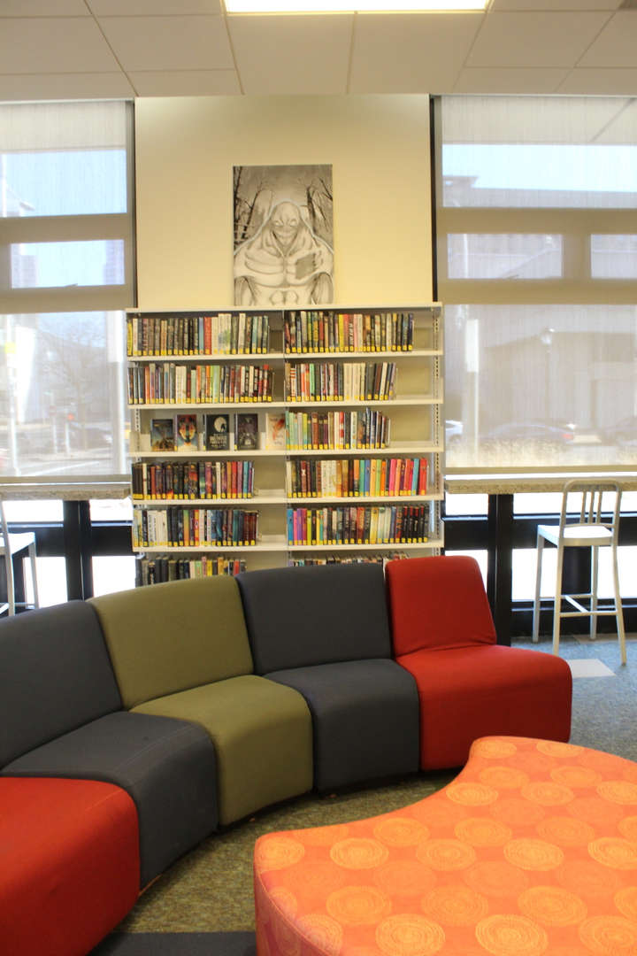 Art displayed on library shelves with seating