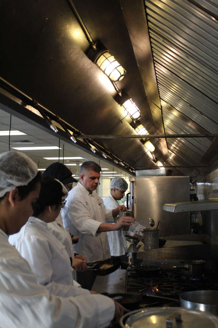 Cooking students working by the stoves