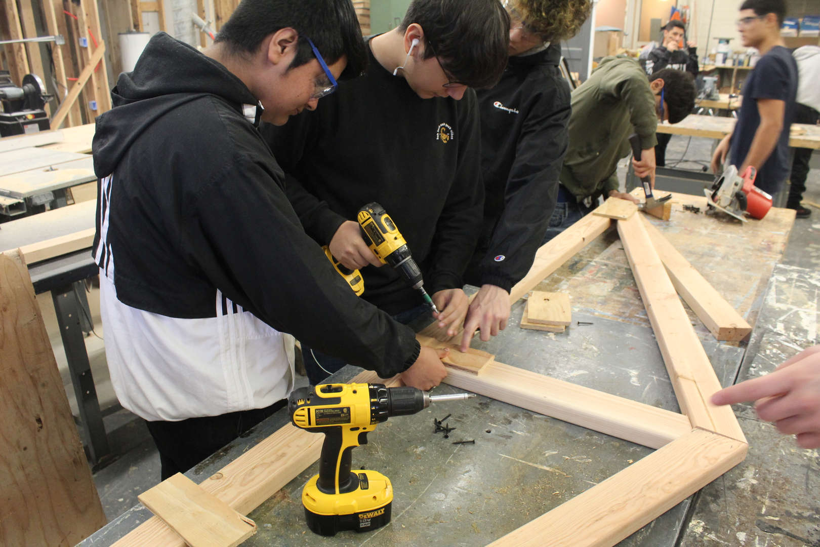 Two boys nail truss together