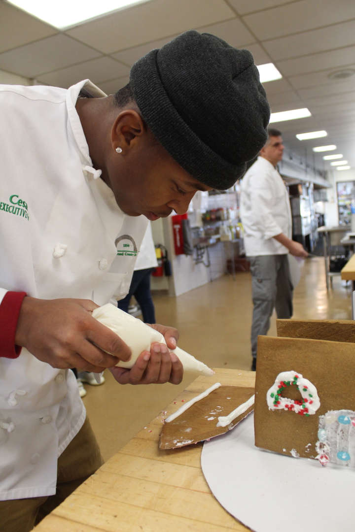 Students puts icing on gingerbread house