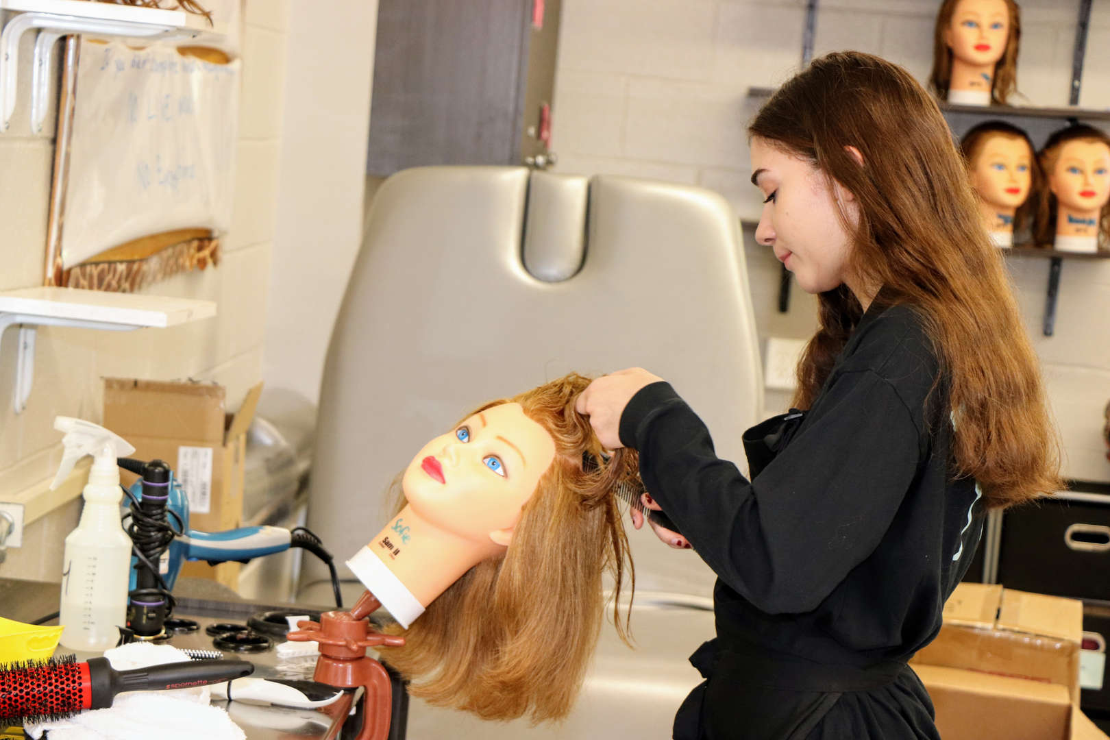 Cosmetology student works on a manikin
