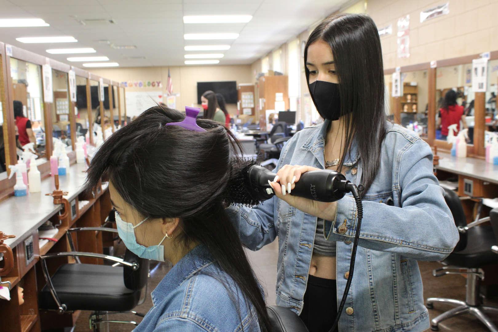 Girl using flatiron tool on another girl's hair