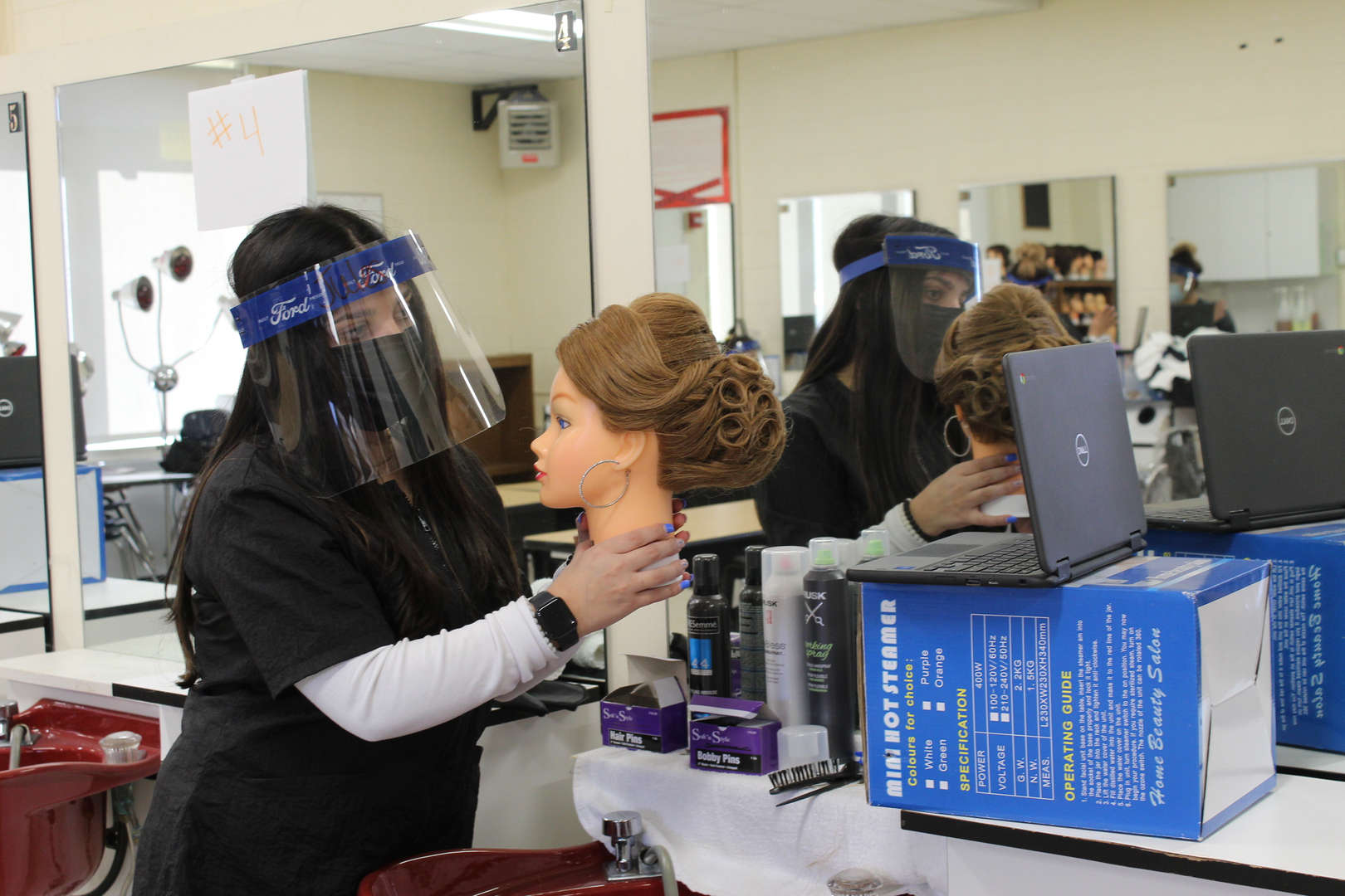 Cosmetology student holds up mannikin in front of computer for judges to see