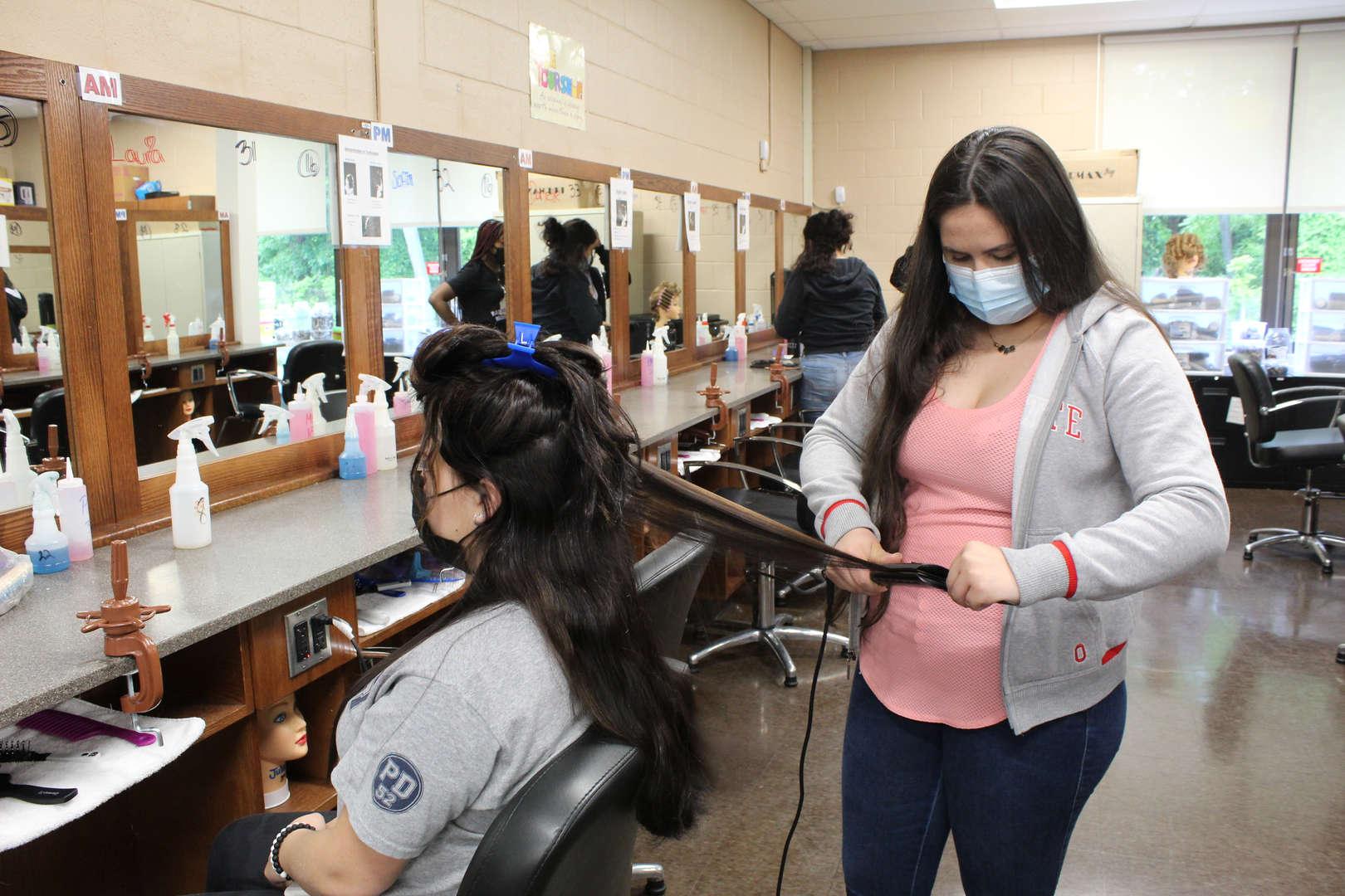 Girl straighten the hair of another girl usin ga flatiron tool