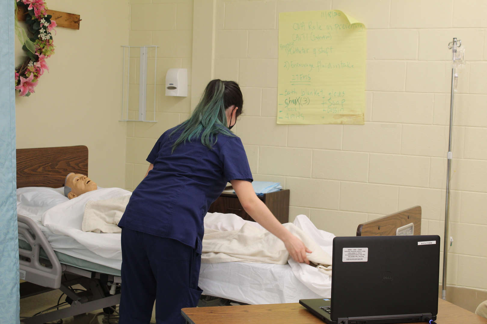 Nursing assistant student helps a dummy patient with exercise