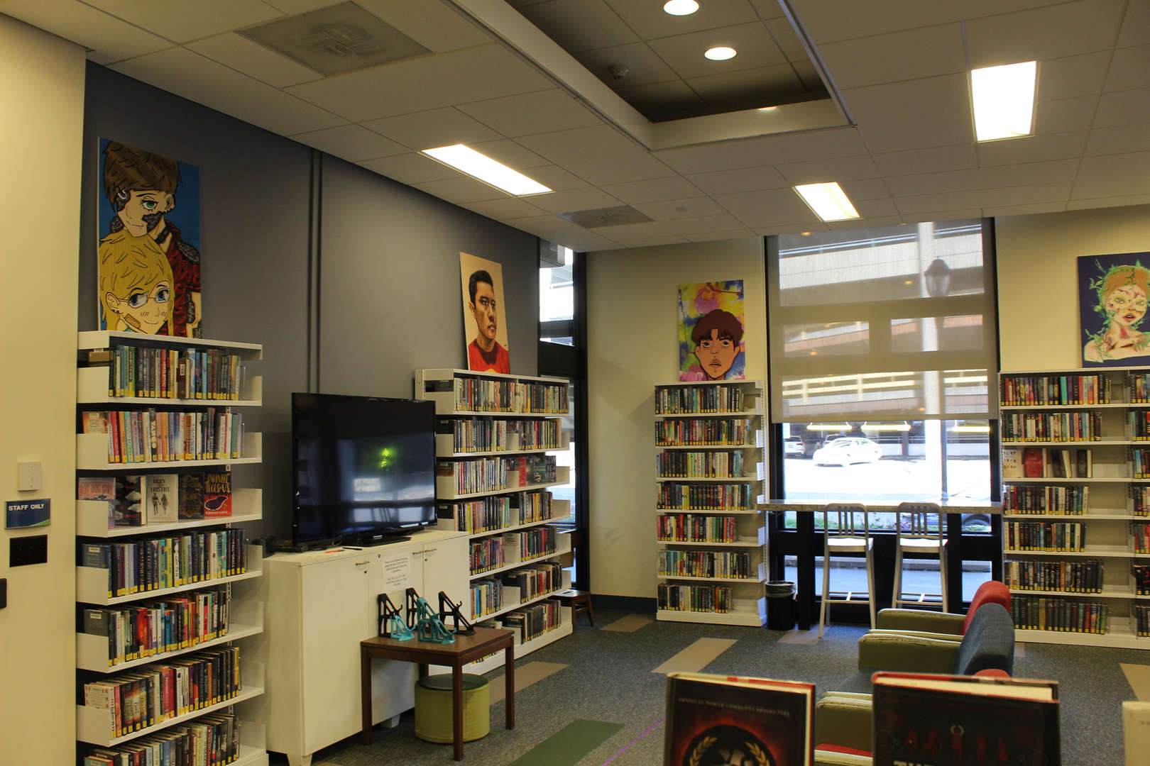 Art displayed above shelves in library