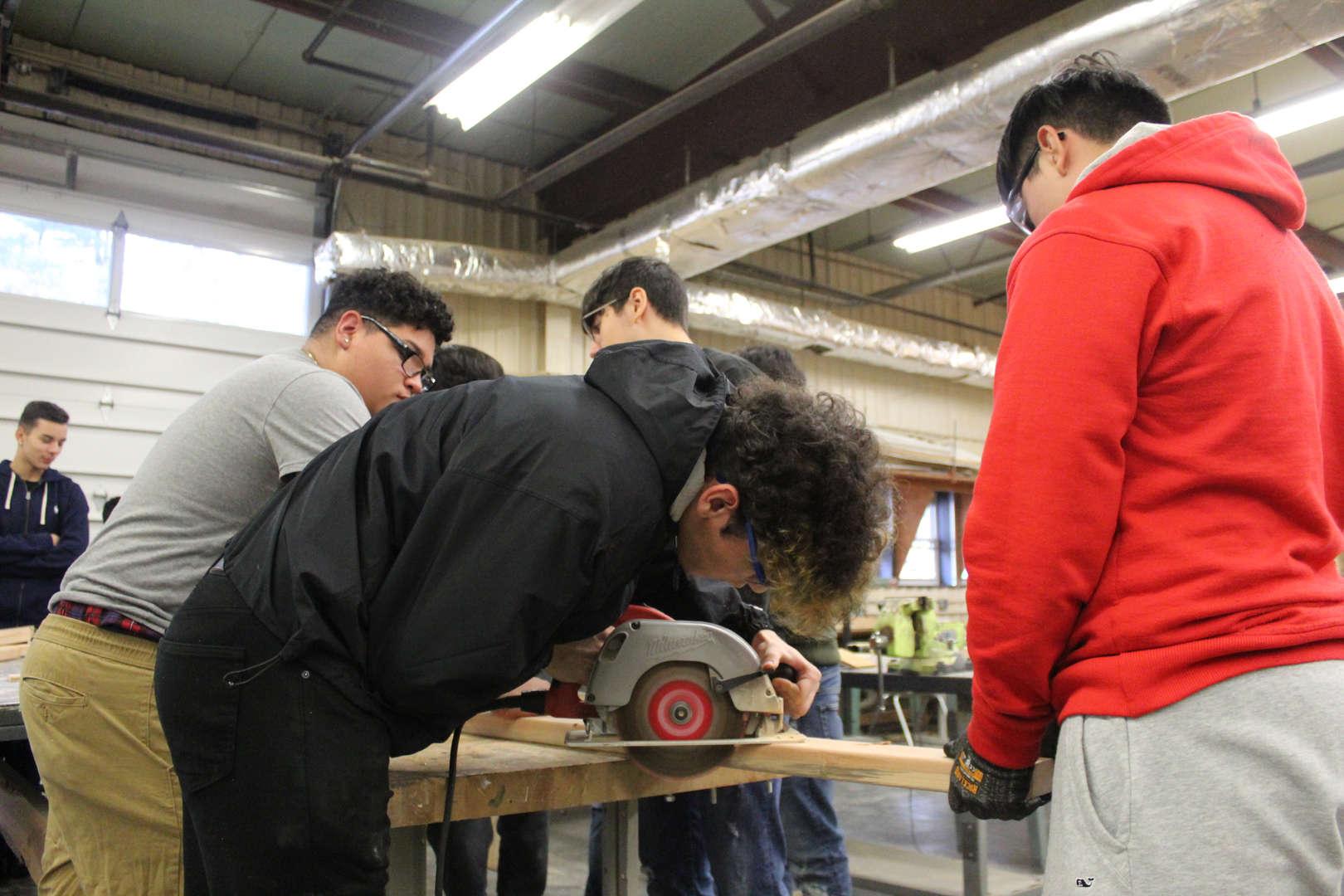 Student uses hand saw