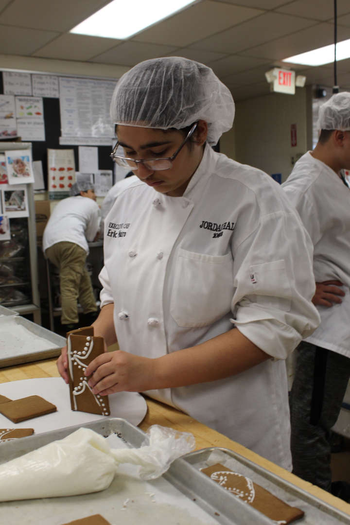 Student works on keeping walls of gingerbread house up