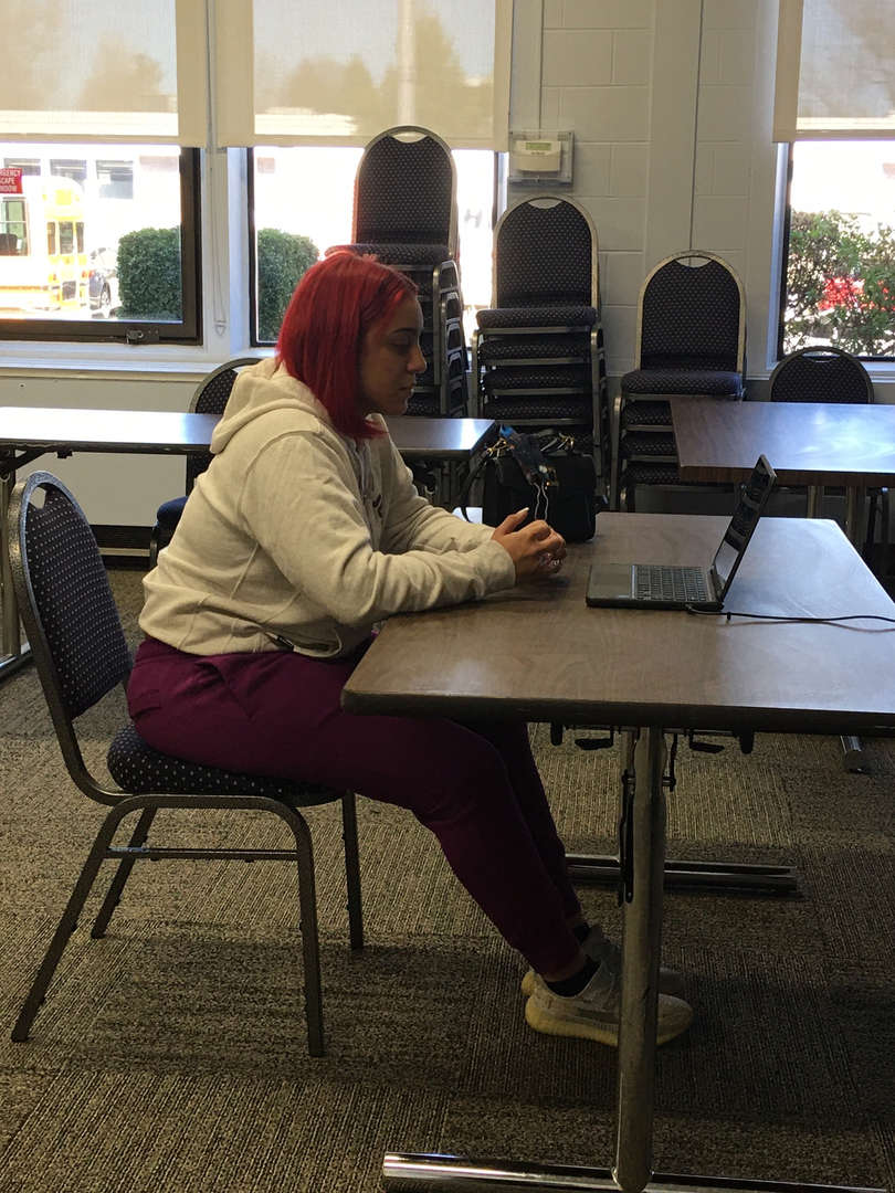 Girl sits at table with a computer on it doing a virtaul job interview