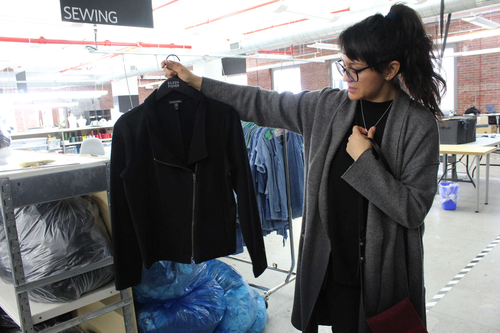 Woman holds up a black jacket