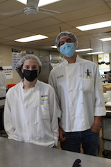 Two culinary students stand in a industrial kitchen
