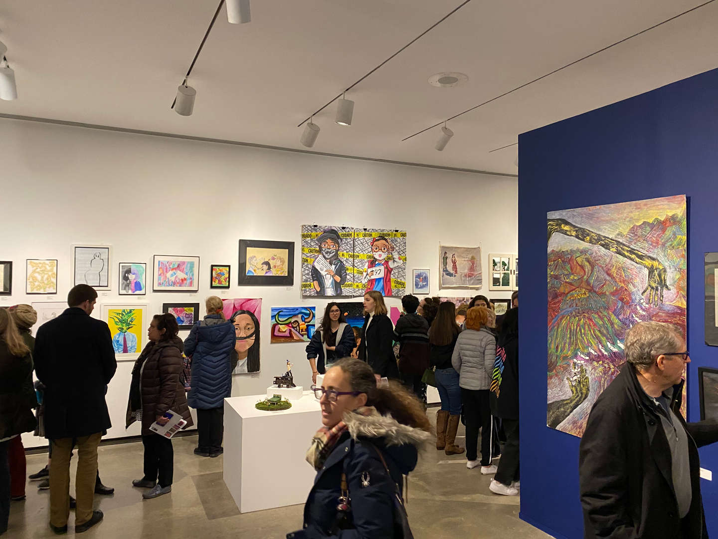 Crowd looks at art in gallery