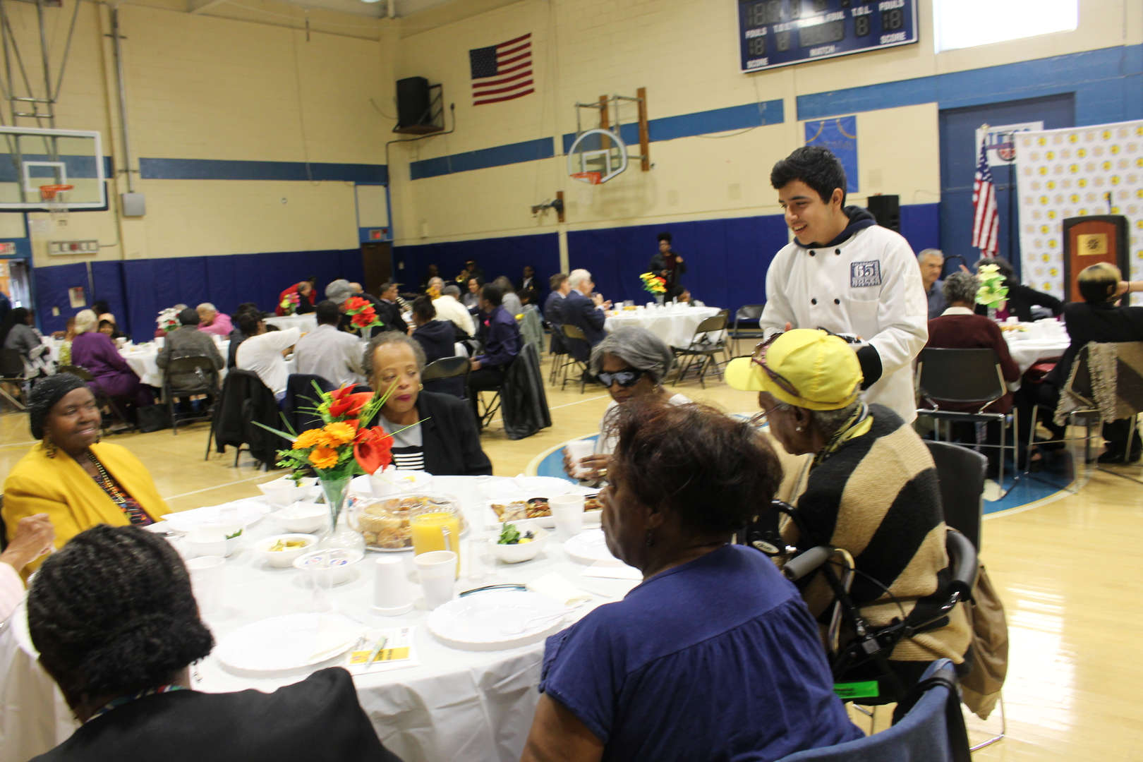 Student serves breakfast to crowd at community breakfast event