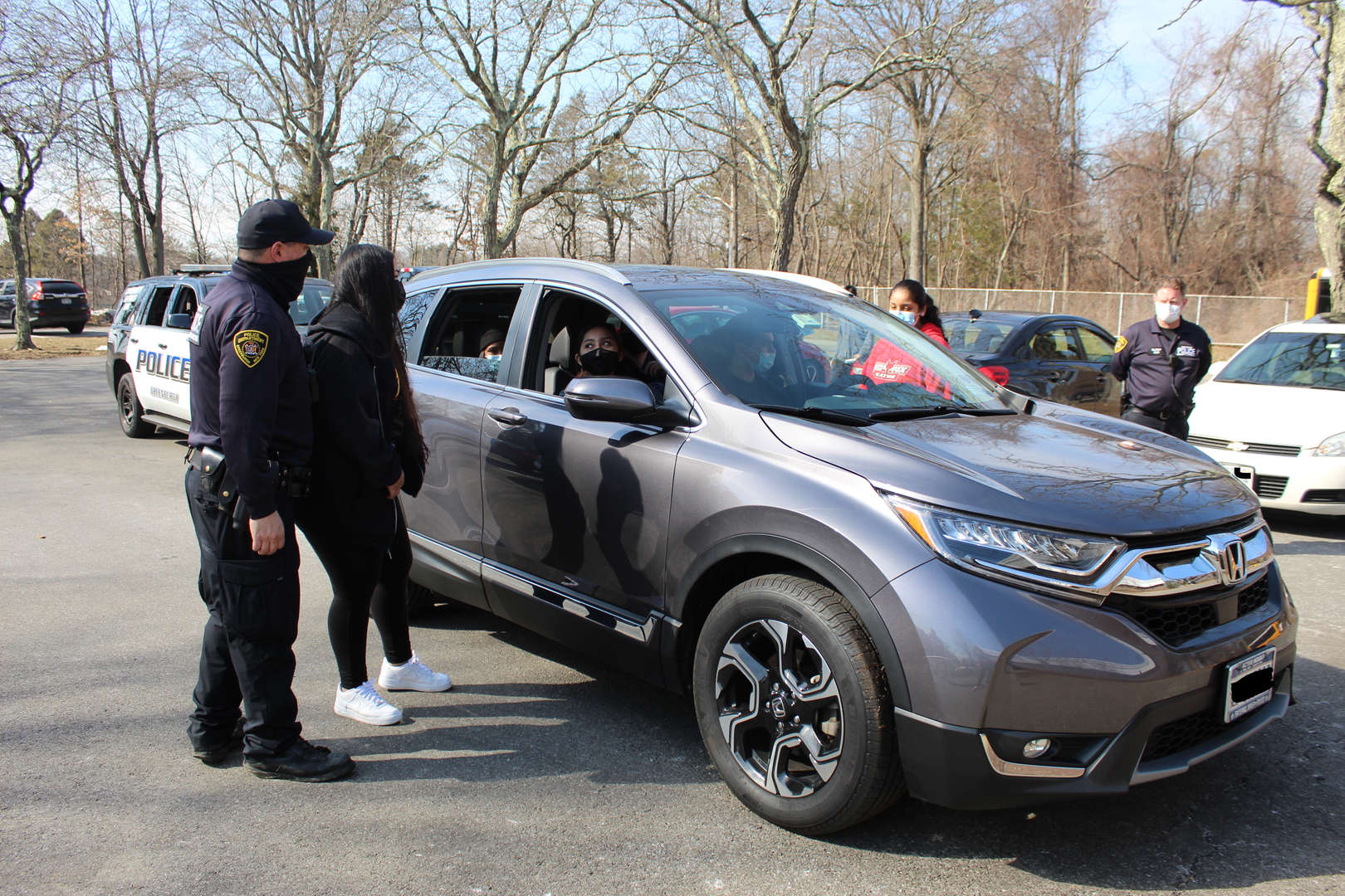 Students and cop stand outside vehicle in a simulated traffic stop