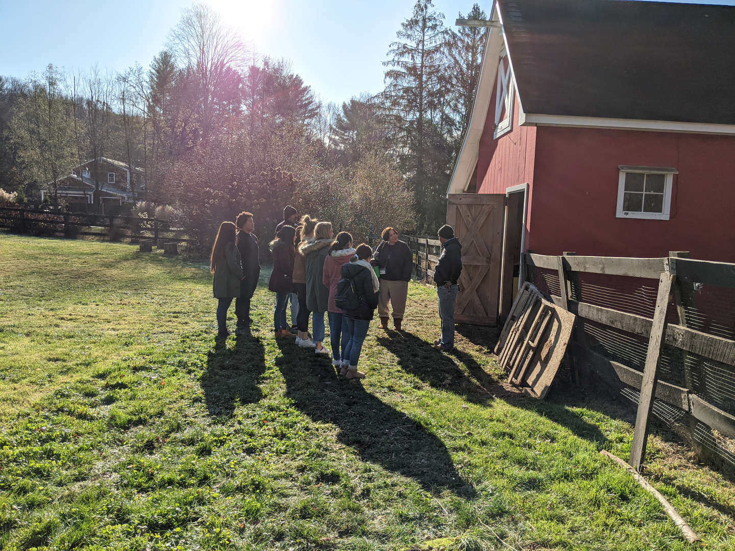 Students gather outside a red barn