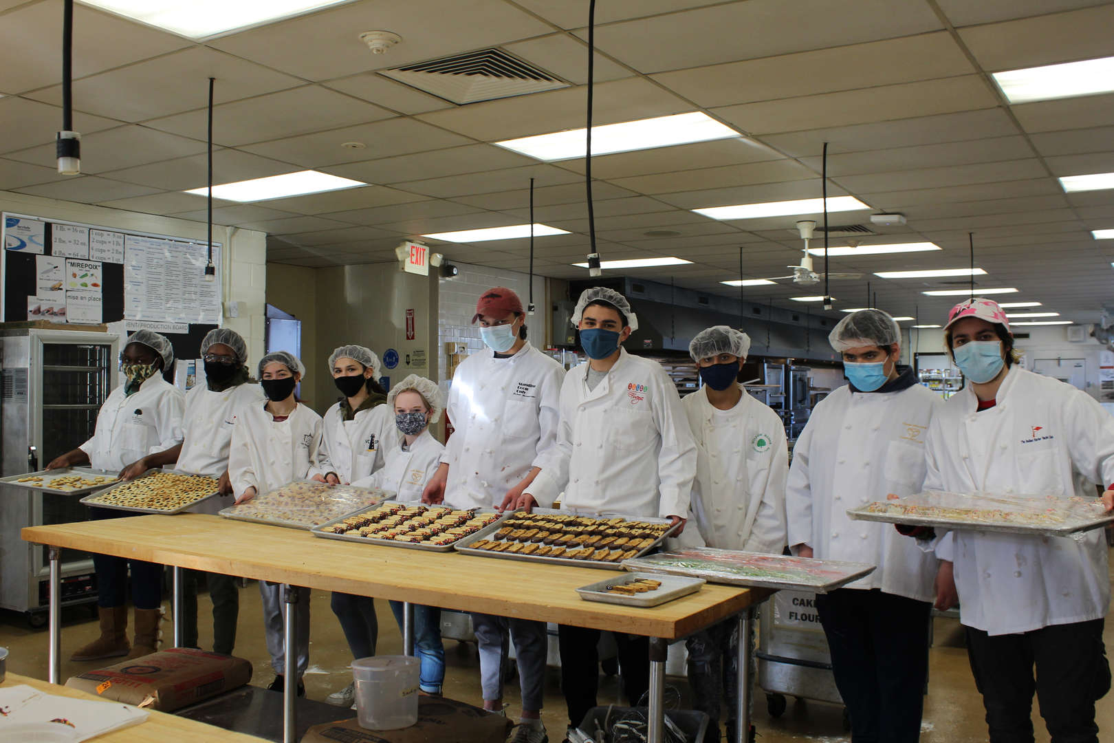 Group of culinary students holding trays of cookies