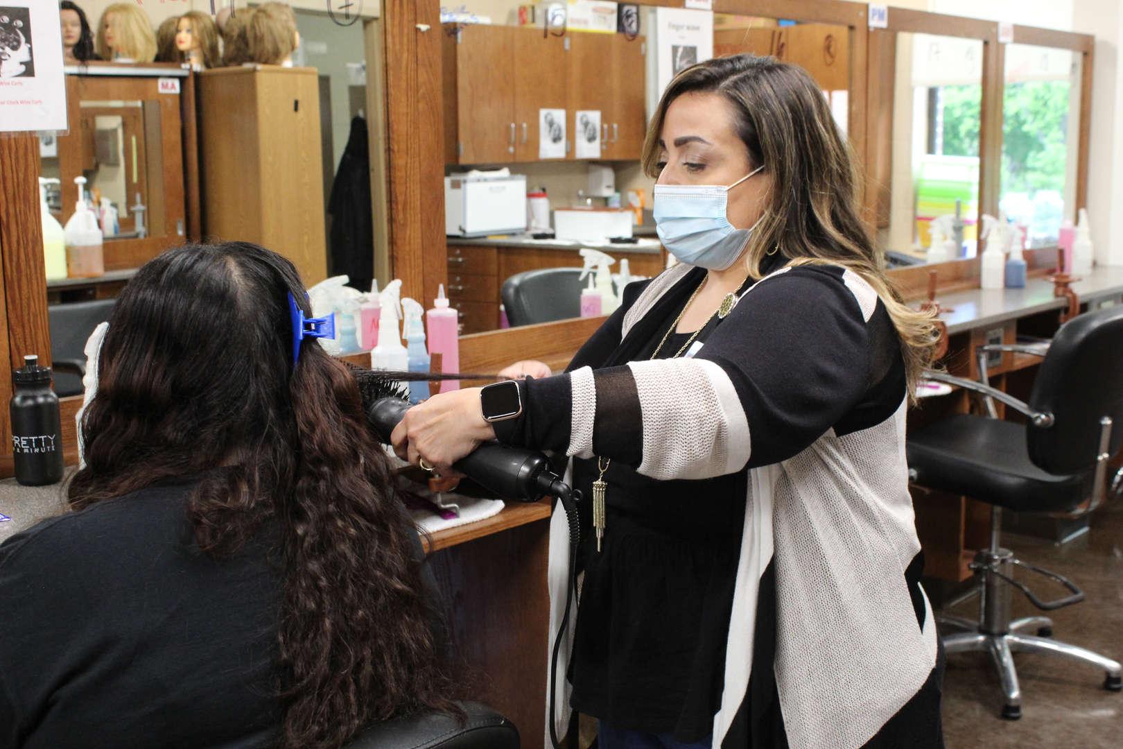 Teacher uses a flatiron tool on a students hair