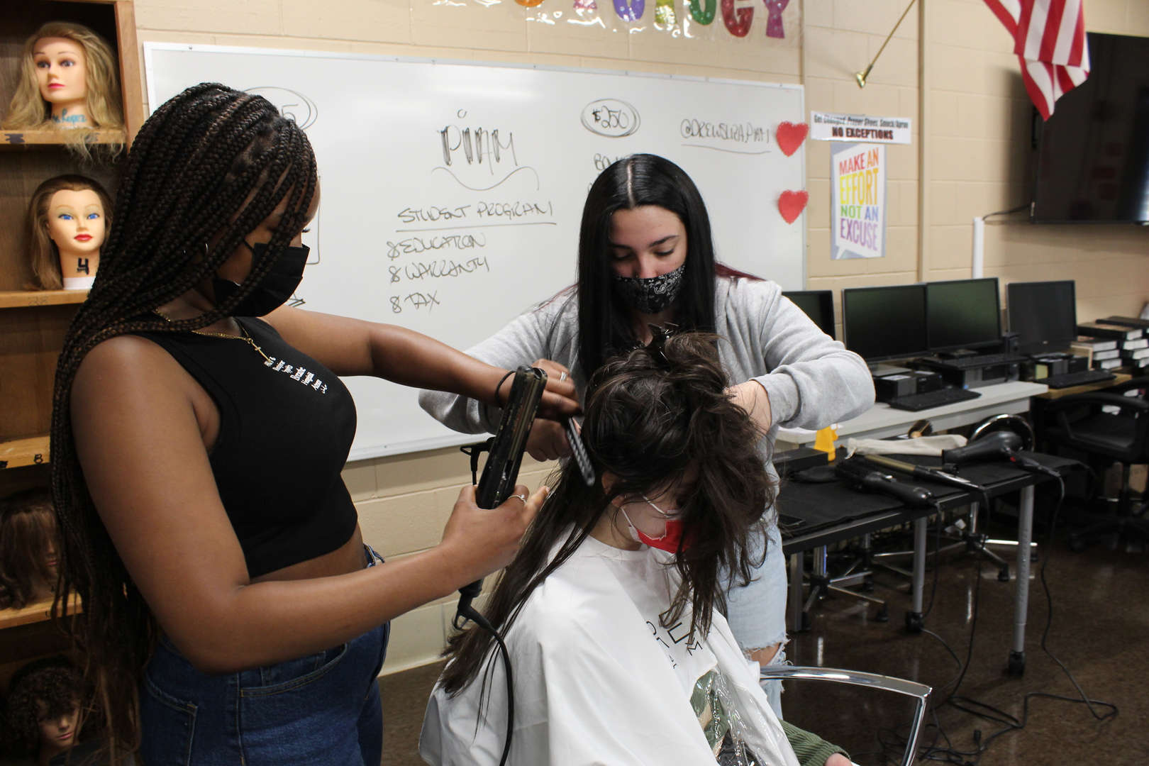 Girl uses flatiron tool to straighten out another girl's hair