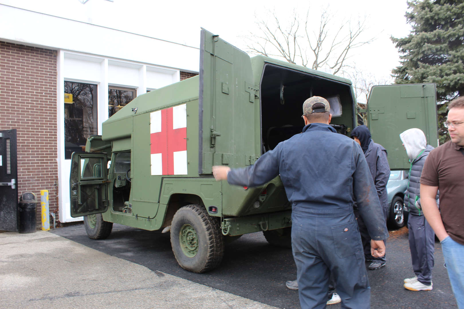 A military Humvee is inspected by students