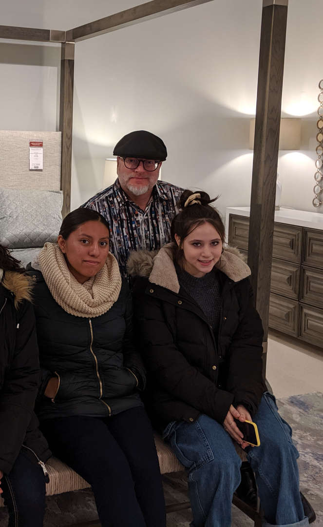 Two girls sitting with man in furniture show room