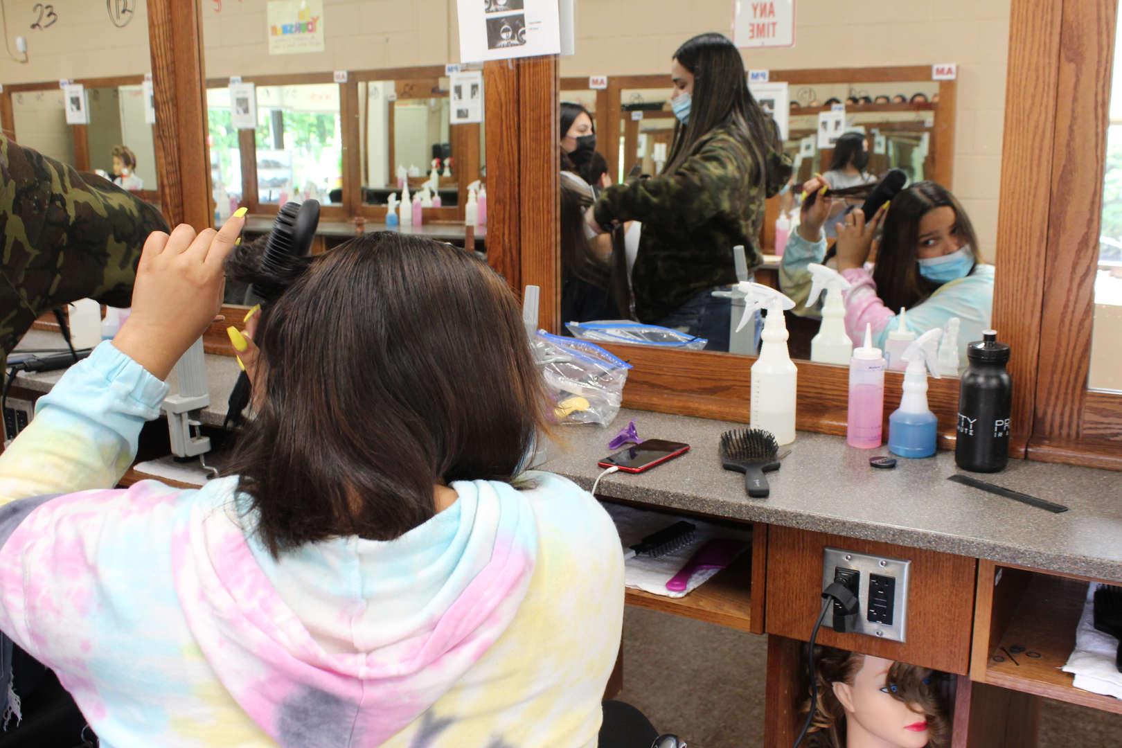 Girl uses straightening hair brush on her hair