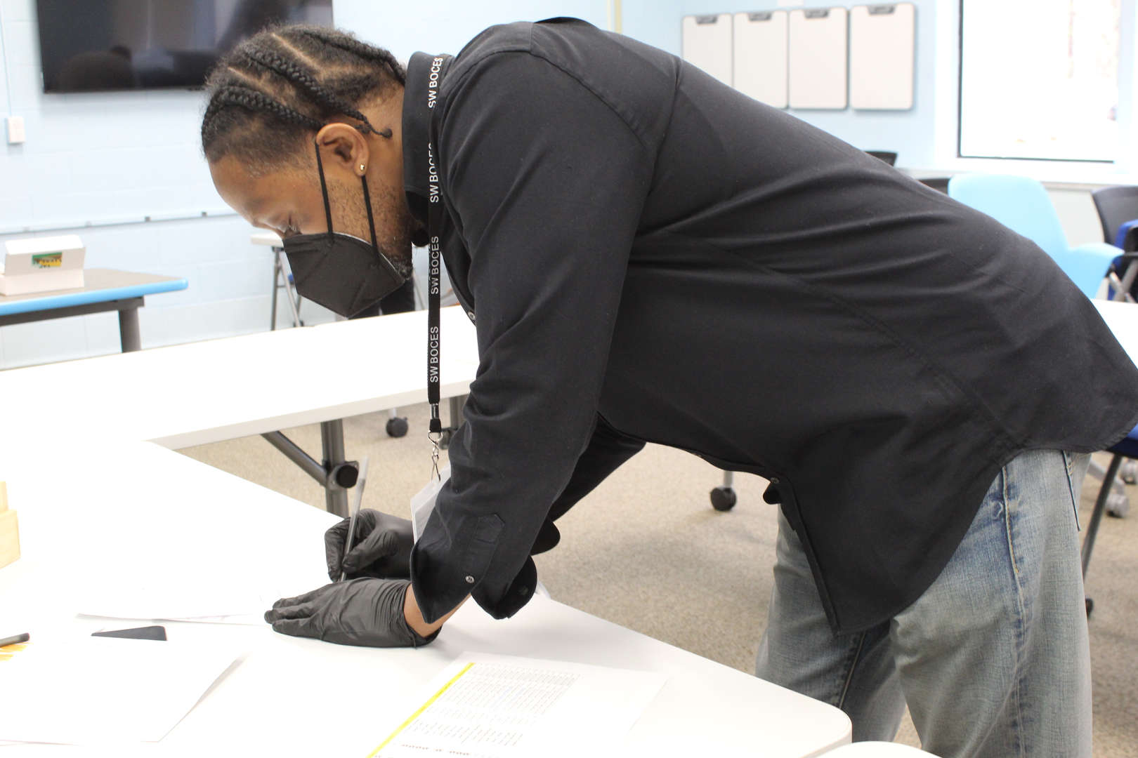 Teacher bends over desk to write on a piece of paper