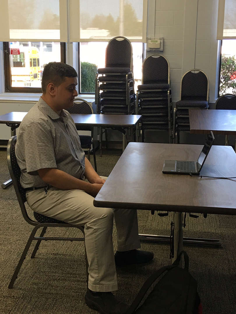 Boy sits at a table with a computer on it doing a virtual job interview