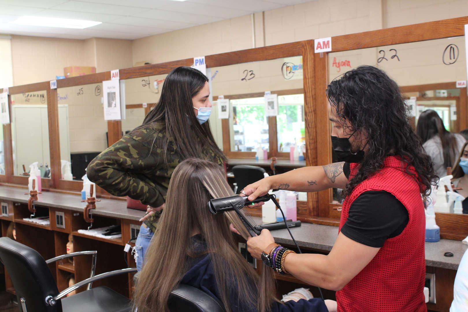 Man uses flatiron tool to straighten hair on girl