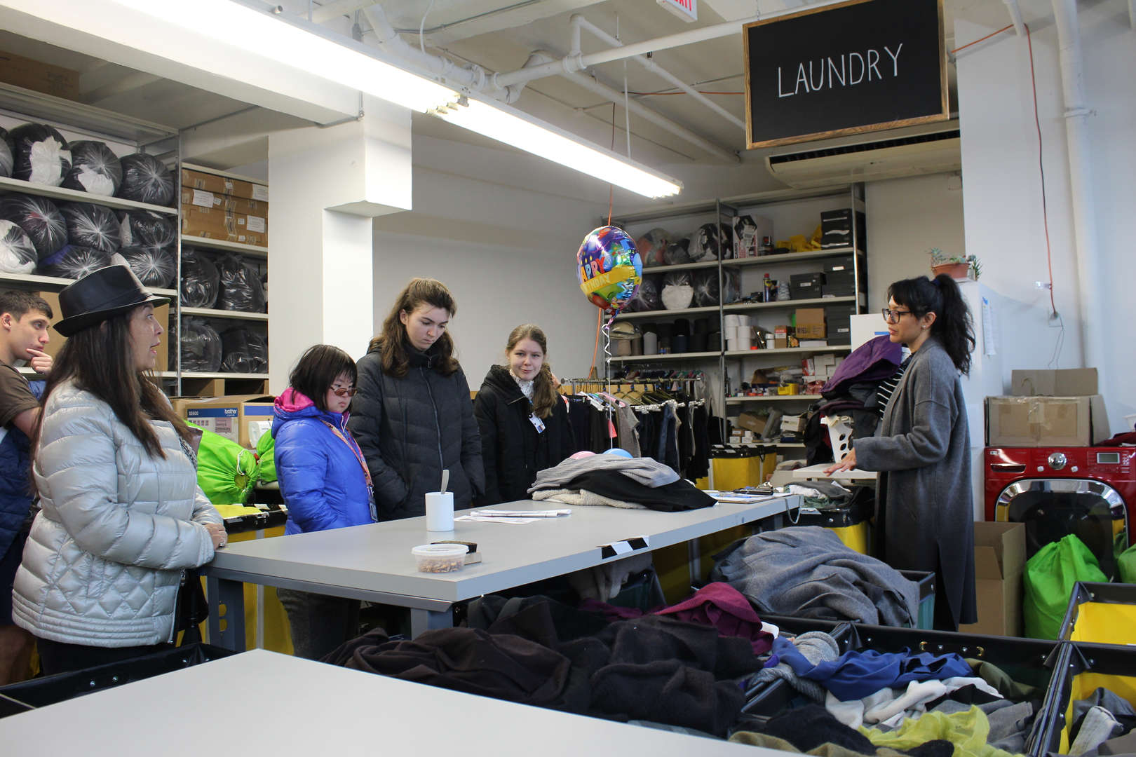 Woman talks to students amongst piles of clothing