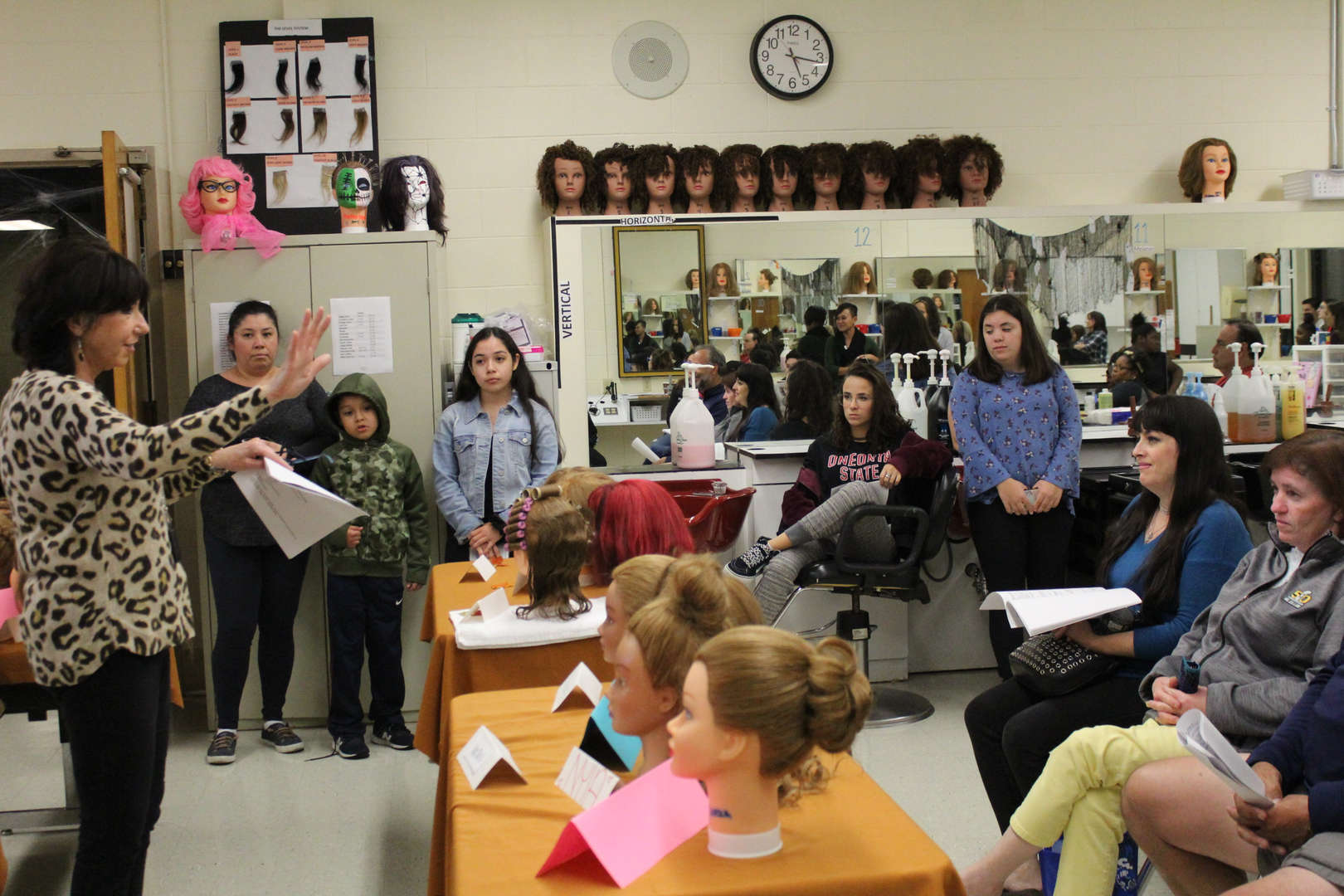 Cosmetology teacher speaks to a group of parents who are seated at desks