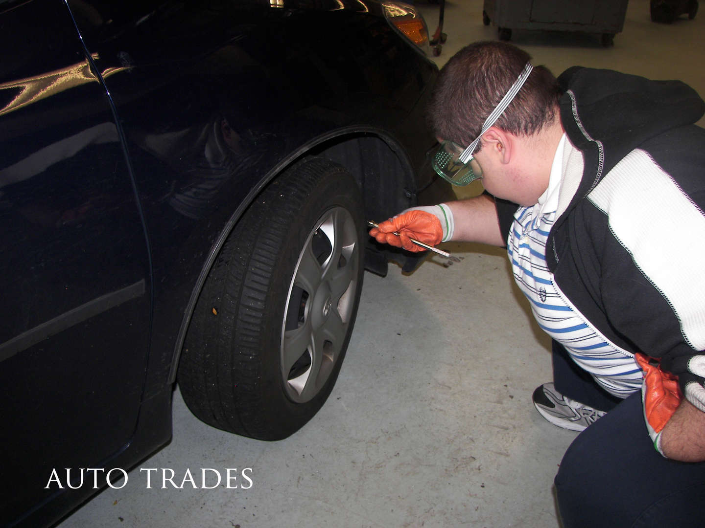 An automotive student works on a car tire