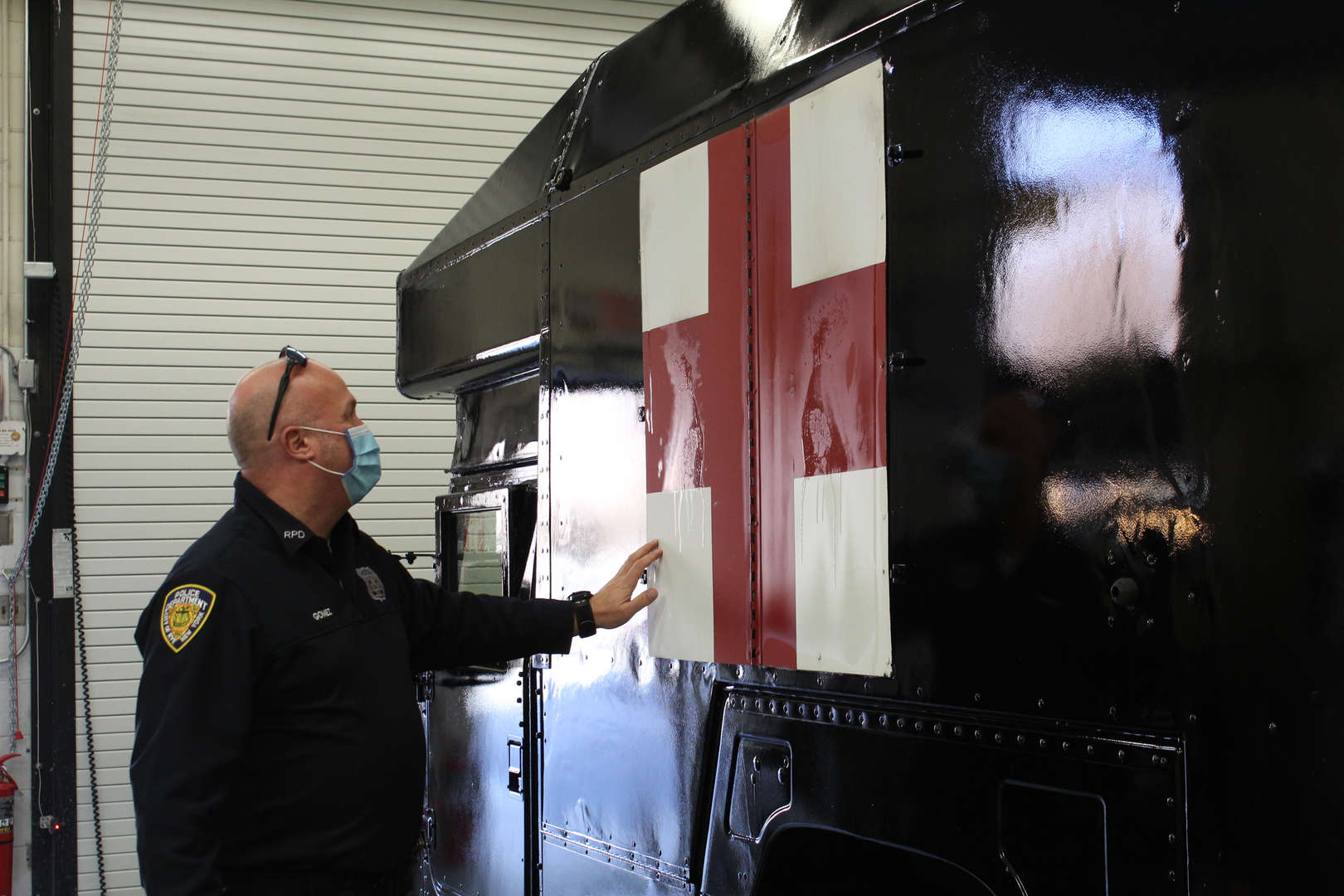 Police officer looks at side of newly painted vehicle