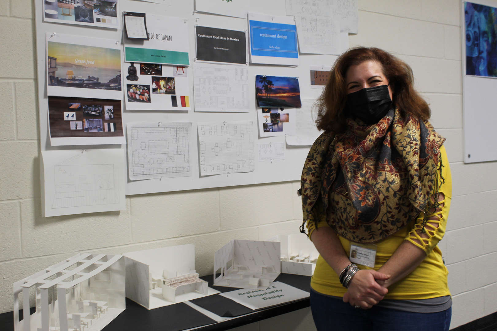 Woman wearing a mask standing in front of architectural renderings