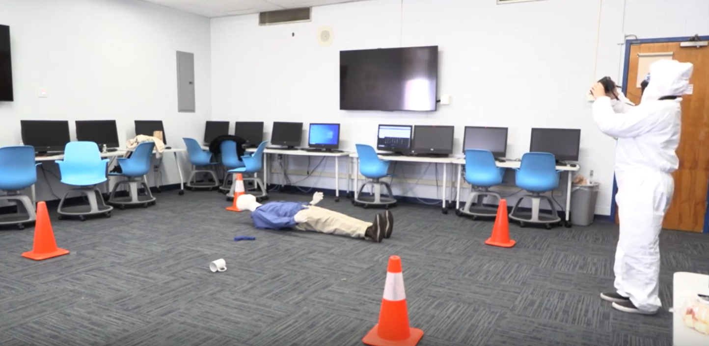 Student, dressed in protective clothing, takes photos of a simulated crime scene