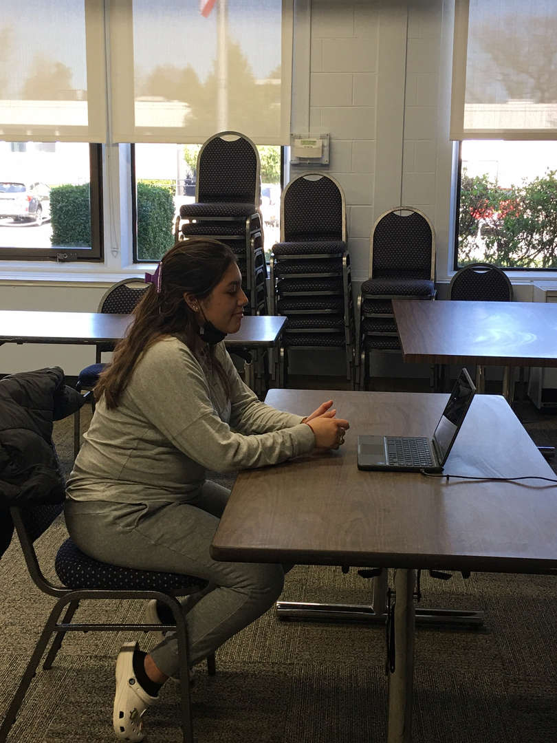 Girl sits at table with a computer for a virtual job interview