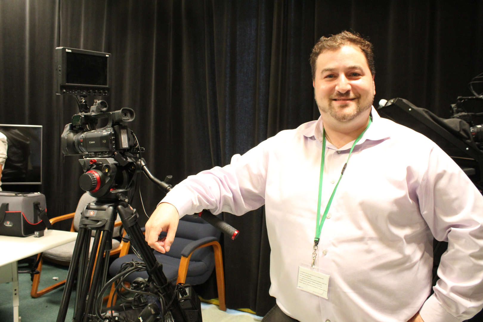 Man standing next to video camera