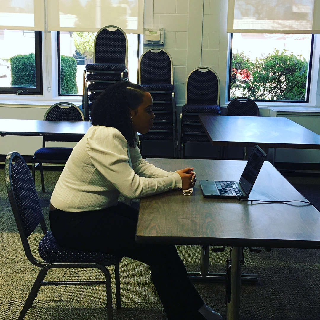 A girl sits at a table with a computer on it doing a virtual job interview