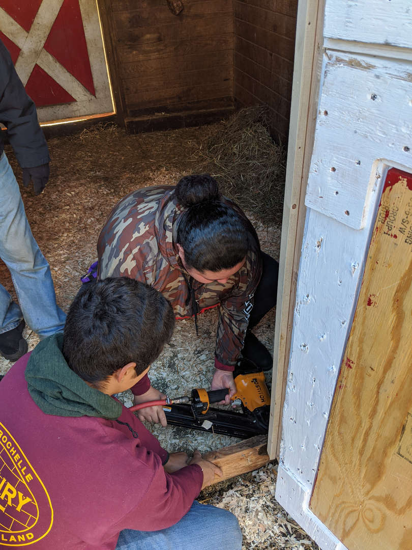 Students drill parts of a door into place